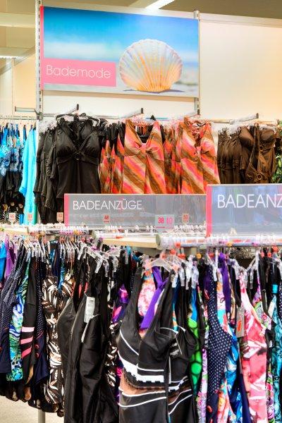 Bereichsbeschilderung für Adler Mode - Thema Strandmode an den Warenträgern und Trennwänden.