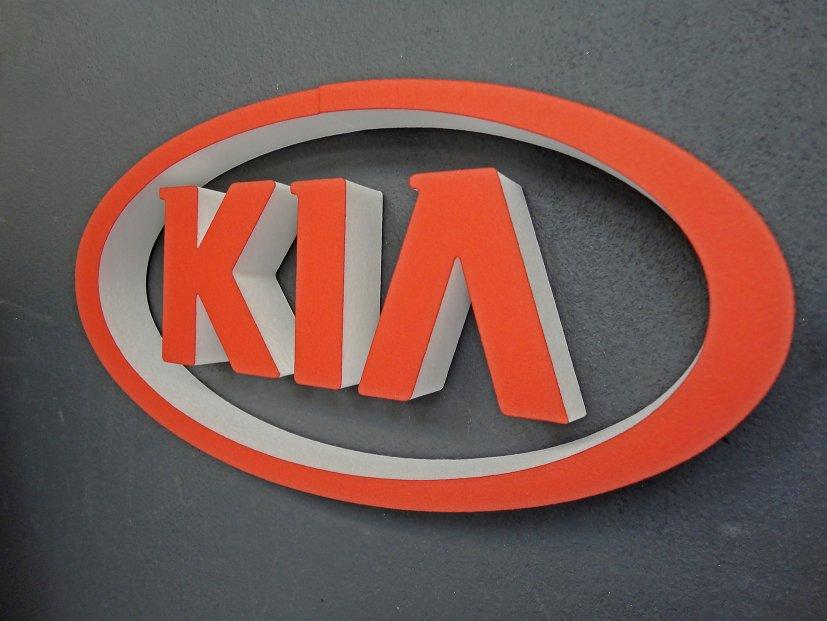 3D-KIA Logo Schriftzug aus XPS-Schaum lackiert und mittels Magnetplättchen an grauer Eisenfarbenwand flexibel befestigt.
