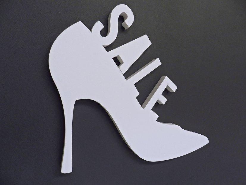 3D-Piktogramm SALE Schuh aus XPS-Schaum, konturgeschnitten und mit Magnetbefestigung auf Eisenfarbenwand.